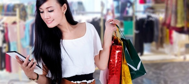 Beautiful woman smiling with her digital tablet and shopping bags